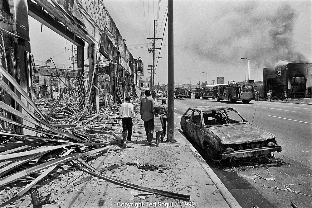 A group of children walk by riot damaged businesses on W.Adams Blvd. in South Los Angeles. 5/1/1992