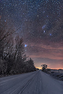 The constellation of Orion and the bright star Sirius in Canis Major, down my country road, on a very cold and frosty moonless January night, with the temperature at -25&deg; C. But no wind! <br /> <br /> This a stack of 5 x 15-second exposures, untracked, for the ground, stacked with mean combine mode to smooth noise, plus a single exposure for the sky, to keep the stars as pinpoint as possible. All at f/2 with Sigma 24mm Art lens and the Nikon D750 at ISO 3200. The image serves as a good workshop example of Rule of Thirds composition.