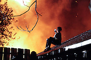A boy uses a smartphone to photograph exposed flames burning through the rear of a 3 - story house during a three-alarm fire at 488 Liberty Street in Newburgh, NY on Sunday, October 23, 2011. Nearly a dozen people were left homeless after the fire erupted in the multi-family home when a resident was cooking in a second-floor apartment in the rear of the building. All the occupants got out safely and there were no injuries.