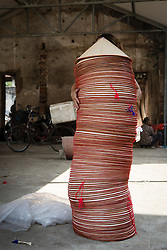 """Hands hold an unsteady stack of conical hats, Chuong Village, Ha Tay Province, Vietnam, Southeast Asia, 2013. This handicraft village specializes in the fabrication of the conical hat, known as """"non"""" in Vietnamese."""