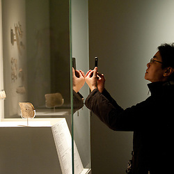 A visitor takes a picture with his iphone to sculptures during the press preview of the 'Ice Age Art - Arrival of the modern mind' exhibition at The British Museum in London. The exhibition, curated by Jill Cook, opens in London on the 7th of February and presents masterpieces of Ice Age sculpture, ceramics, drawing and personal ornaments, created over 20,000 years ago.