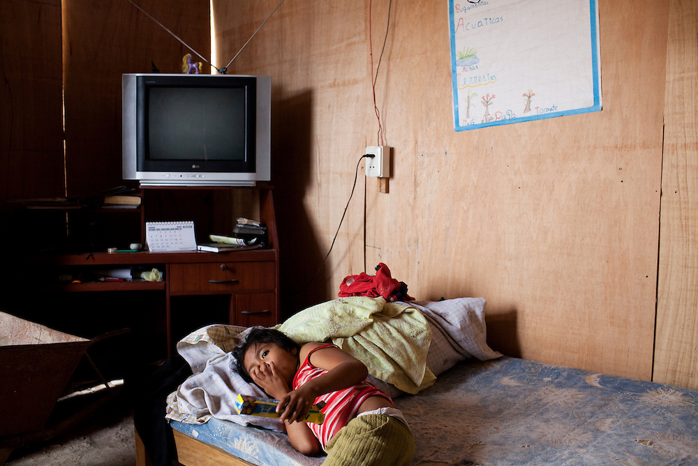 A girl lies on a bed on Monday, Apr. 13, 2009 in Ventanilla, Peru.