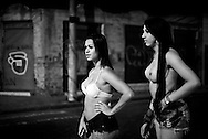 """Lara Santos, Karol. The two transsexuals wait for a client to pass by. In Campinas the dress code requires showing more body, unlike what happens in São Paulo. To """"meet"""" clients in this street, they must pay a commission to a woman who runs it."""