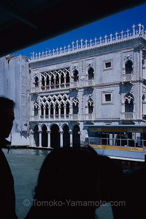 Ca' d'Oro is a palace on the Grand Canal in Venice, Italy. It has a blend of Gothic and Byzantine styles.  On the Grand Canal it has its own vaporetto stop.  View of this shiny house from the vaporetto, with the eyes of tourists  on the house.  Travel Photo of Venice, Italy by Tomoko Yamamoto. Original on 35mm slide film.