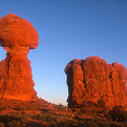 Balanced Rock (left), a prominent feature of Arches National Park near Moab, Utah, is turned red by the golden light of sunrise. The balanced rock is a cap rock that is 55 feet (17 meters) tall and makes up nearly half the overall height of the formation. The formation is made up of several layers of sandstone, which erode at different rates; the layer between the cap rock and the pedestal erodes at a much faster rate than the others.