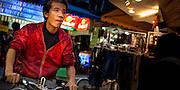 Wufenpu Fashion District night-time market, Taipei, Taiwan. Cyclist making way through an alley.