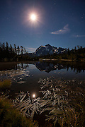 The nearly full moon shines over Mount Shuksan, a 9,131 foot (2,783 meter) mountain in Washington's North Cascades, which is reflected in Picture Lake. Shown here at about midnight, Mount Shuksan was formed about 120 million years ago when two of Earth's plates collided and were thrust upward in an event known as the Easton collision.