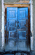 """Blue paint weathers, fades, and exfoliates on an old door in Huaraz, Peru, South America. Published in """"Light Travel: Photography on the Go"""" book by Tom Dempsey 2009, 2010."""