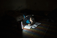 A young girl doing her home work in her house by the light of a battery torch. Una bambina fa' i compiti alla luce di una torcia a batterie