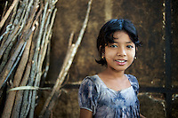 A young Burmese girl poses for a portrait in the kitchen of a roadside bus stop between Bagan and Kawla, Myanmar.