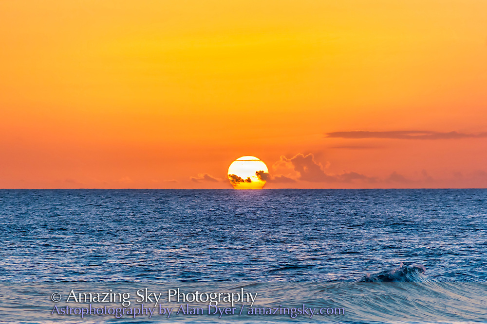 The Sun setting into the ocean, as seen from Barbados, Nov 15, 2013, from near Bridgetown, at a beach overlooking the Caribbean. Shows a mild refraction effect distorting the lower limb of the Sun. Taken with the 18-200mm lens and Canon 60Da, so not a lot of focal length for the subject.