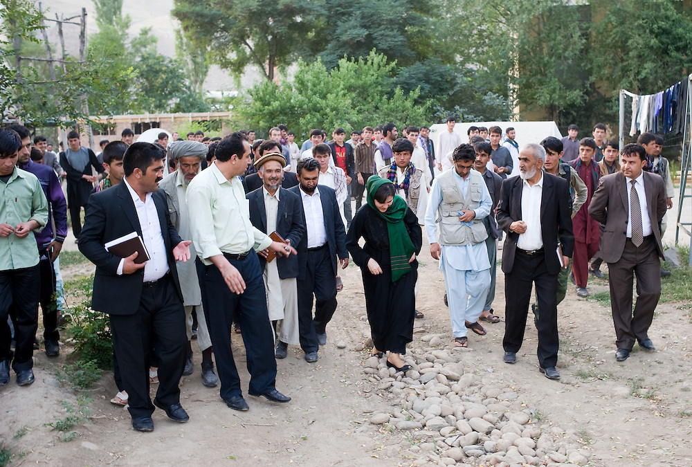 MP Ms. Fawzia Koofi walks gracefully on stones in her heels amidst dozens of men escorting her back to her car after a visit to the boys hostel of the Faizabad University.  Afghanistan, 2012