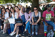 Japanese tourist girls do a selfie while sitting under a tree near Pike Place Market in Seattle, surrounded by colorful locals such as this Rasta man.