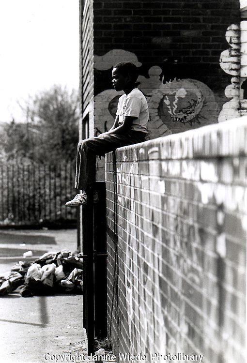Young boy alone on wall playing truant from school.