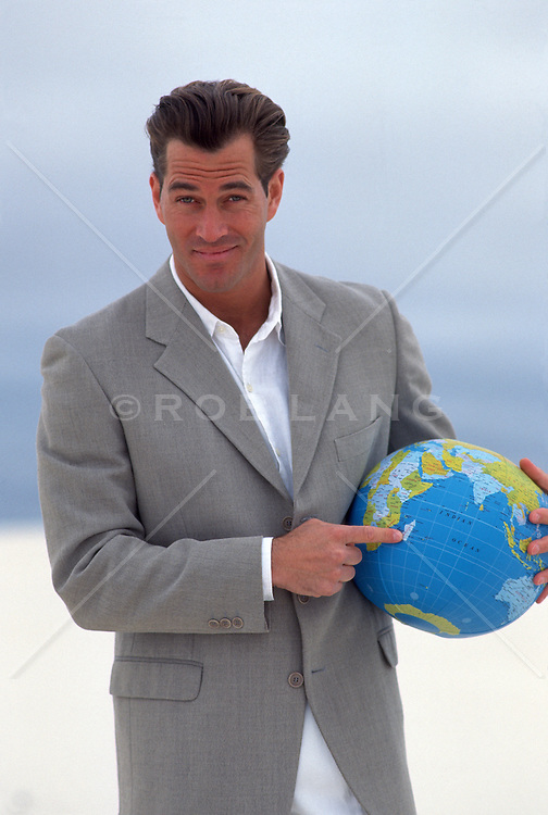Handsome man in a jacket pointing at a location on a globe Under his arm at white Sands, NM