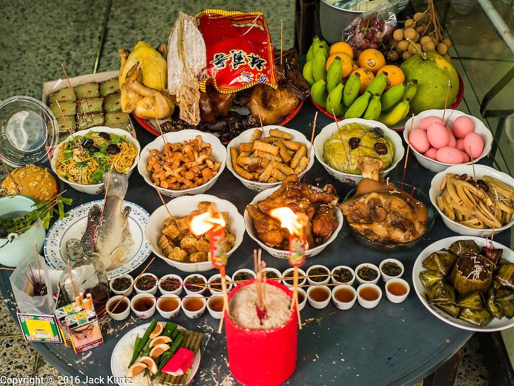 "07 FEBRUARY 2016 - BANGKOK, THAILAND: A feast laid for a family's ancestors in the doorway of their home on Chinese New Year's Eve. Chinese New Year, also called Lunar New Year or Tet (in Vietnamese communities) starts Monday February 8. The coming year will be the ""Year of the Monkey."" Thailand has the largest overseas Chinese population in the world; about 14 percent of Thais are of Chinese ancestry and some Chinese holidays, especially Chinese New Year, are widely celebrated in Thailand.        PHOTO BY JACK KURTZ"