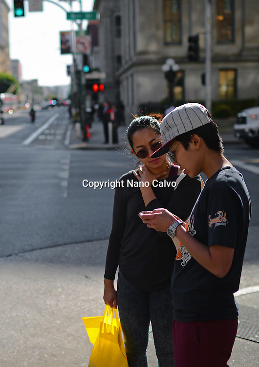 Two people checking smartphone in street, San Francisco.