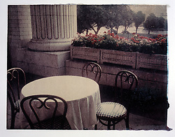 Polaroid transfer outdoor patio restaurant, bent cane chairs, columns, floral window boxes.
