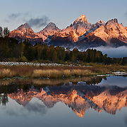 Mountain peaks reflect in the Snake River at Schwabacher Landing at sunrise, Grand Teton National Park, Wyoming, USA