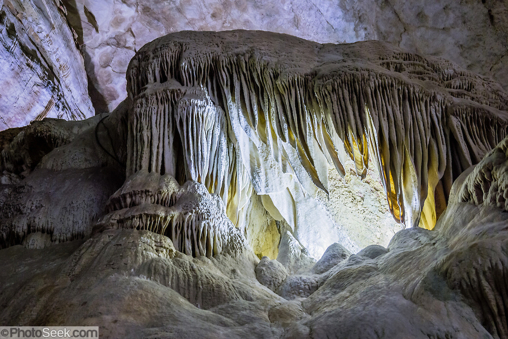 Whales Mouth, draperies and flowstone, Carlsbad Caverns National Park, in the Guadalupe Mountains, Chihuahuan Desert, southeast New Mexico, USA. Hike in on your own via the natural entrance or take an elevator from the visitor center. Geology: 4 to 6 million years ago, an acid bath in the water table slowly dissolved the underground rooms of Carlsbad Caverns, which then drained along with the uplift of the Guadalupe Mountains. The Guadalupe Mountains are the uplifted part of the ancient Capitan Reef which thrived along the edge of an inland sea more than 250 million years ago during Permian time. Carlsbad Caverns National Park protects part of the Capitan Reef, one of the best-preserved, exposed Permian-age fossil reefs in the world. The park's magnificent speleothems (cave formations) are due to rain and snowmelt soaking through soil and limestone rock, dripping into a cave, evaporating and depositing dissolved minerals. Drip-by-drip, over the past million years or so, Carlsbad Cavern has slowly been decorating itself. The slowest drips tend to stay on the ceiling (as stalactites, soda straws, draperies, ribbons or curtains). The faster drips are more likely to decorate the floor (with stalagmites, totem poles, flowstone, rim stone dams, lily pads, shelves, and cave pools). Today, due to the dry desert climate, few speleothems inside any Guadalupe Mountains caves are wet enough to actively grow. Most speleothems inside Carlsbad Cavern would have been much more active during the last ice age-up to around 10,000 years ago, but are now mostly inactive.