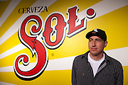 Painter Abel A. Gonzalez with his work after a famous beer logo at Centro Cultural in Nuevo Laredo, Mexico.<br /> <br /> La Frontera: Artists along the US Mexican Border. <br /> &copy; Stefan Falke   <br /> www.stefanfalke.com
