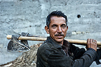 Nepali laborers are common throughout many parts of the Himalaya. In this photograph a Nepali laborer is seen with his wood cutting tools.