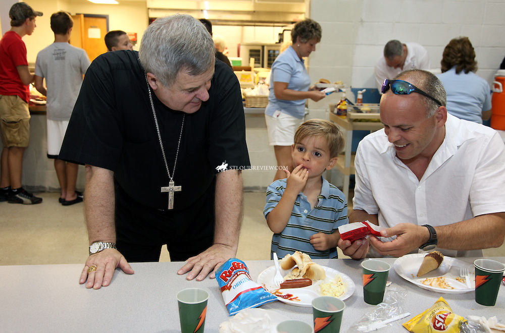 Archbishop Robert J. Carlson greeted  Sam and his father, Peter, after dedicating the new parish center at St. Paul Church in Fenton June 29. The Benediction and prayers were held in the new gymnasium, which is nearly complete. After the dedication, there were tours of the center and a barbecue in the cafeteria.