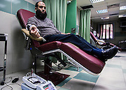 An Egyptian man donates blood at a National Blood Transfusion Services (NBTS) Center June 16, 2015 in Cairo, Egypt. At smaller private blood banks many blood transfusions are screened with older antibody tests that miss some infections, complicating the national fight against blood borne viruses such as Hepatitis C. (Photo by Scott Nelson, for the New York Times)