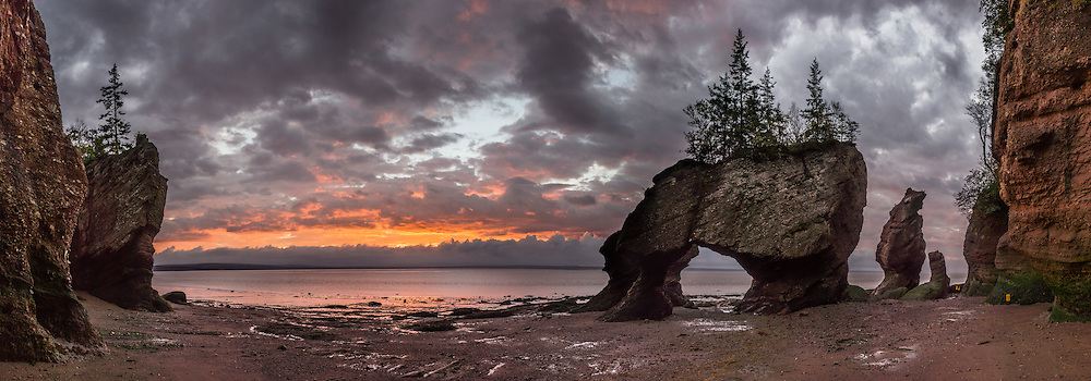 Sunrise. Visit Hopewell Rocks (Flowerpot Rocks) at Hopewell Cape, near Moncton, New Brunswick, Canada. Hopewell Rocks have one of most extreme tidal ranges in the world: up to 16 meters (52 feet) vertically. Waves and tides twice per day have eroded the base of the rocks faster than the tops, leaving arches and curiously shaped formations of dark sedimentary conglomerate and sandstone rock. For best photo lighting, go in morning (or spectacular sunrise) during the first low tide of the day, safe for 3 hours before low tide until 3 hours after. Walking the beach is easy until its southern end, where The Ledges, a ridge of slippery limestone, can be clambered over to reach Demoiselle Beach. Bay of Fundy has the highest tidal range in the world, due to a resonance of being just the right length (270 km) matching the gravitational pushing cycle of the Moon that causes the tides. Due to the bay's optimal size, the time it takes a large wave to go from the mouth of the bay to the inner shore and back is practically the same as the time from one high tide to the next. (See the effect of resonance by steadily pushing a long pan of water back and forth: an optimal pushing frequency for a given pan size will build up a high wave of water which sloshes out; but pushing too fast or too slow won't build up the big wave.) Two high tides occur per day, one when the ocean side of the Earth is nearest the Moon, and one on the side most distant from the Moon, about 12 hours and 25 minutes from one high tide to the next. The Bay of Fundy is on the Atlantic coast of North America, on the northeast end of the Gulf of Maine between the Canadian provinces of New Brunswick and Nova Scotia. Address: Hopewell Rocks Ocean Tidal Exploration Site (phone 506-734-3429), 131 Discovery Rd, Hopewell Cape, NB E4H 4Z5.  The panorama was stitched from 14 overlapping photos.