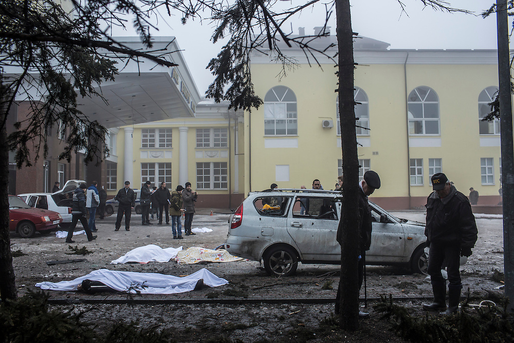 DONETSK, UKRAINE - JANUARY 30, 2015: Investigators search for evidence at the scene of a rocket attack that killed at least five people when it struck the parking lot near a humanitarian aid distribution center in Donetsk, Ukraine. At least two others died in a separate shelling nearby. CREDIT: Brendan Hoffman for The New York Times