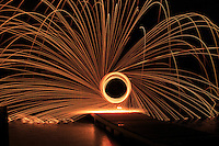 This photo was taken from a tripod with a long exposure. I placed fine steel wool into a metal whisk and tied a string to the end of the whisk. Then I lit the steel  wool on fire and spun it around  while the exposure was being made. The sparks went flying, it was a lot of fun.