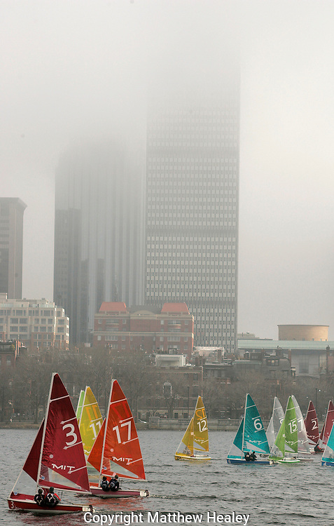 (032809  Cambridge, MA) Competitors in the Boston Dinghy Cup sailing race head down river past a fogged in skyline.  Photo by Matthew Healey