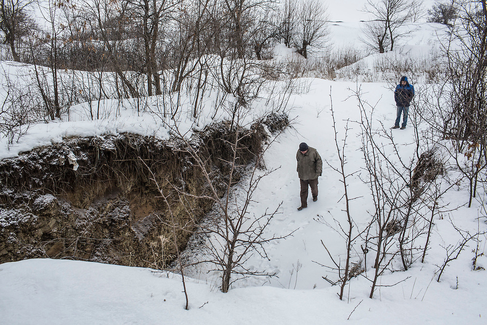 SNEZHNE, UKRAINE - JANUARY 25, 2015: Edik Moroz, right, watches as Vladimir Moroz walks down into the coal mine he used to operate across the street from his house in Snezhne, Ukraine. The area is well known for its many coal mines, both large operations and small backyard operations. CREDIT: Brendan Hoffman for The New York Times