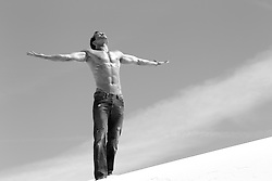 shirtless man with a great body wearing nothing but jeans with his arms open to the sky