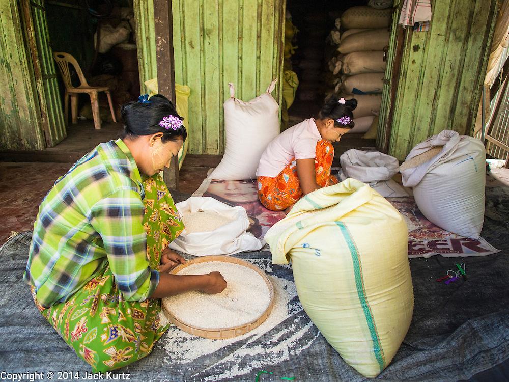 10 NOVEMBER 2014 - SITTWE, MYANMAR: Women sift rice in the rice market in Sittwe, Myanmar. Sittwe is a small town in the Myanmar state of Rakhine, on the Bay of Bengal.    PHOTO BY JACK KURTZ