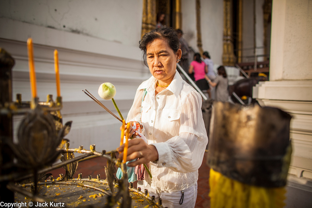 "01 JANUARY 2013 - BANGKOK, THAILAND:   A woman lights candles to make merit during a New Year's Day merit making service at Wat Suthat in Bangkok. Many Thais go to Buddhist temples and shrines to ""make merit"" for the New Year. The traditional Thai New Year is based on the lunar calender and is celebrated in April, but the Gregorian New Year is celebrated throughout the Kingdom.    PHOTO BY JACK KURTZ"