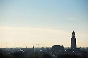 Uitzicht op de historische binnenstad van Utrecht, met rechts de Dom en in de achtergrond windturbines voor groene energie.<br /> <br /> View on the historical city of Utrecht, with the Dom on the right and wind turbines at the horizon.