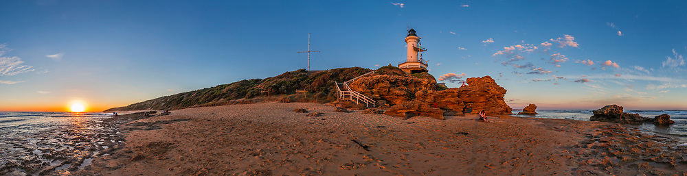 The Sun setting and warming the landscape at the Point Lonsdale Lighthouse near Queenscliffe, Victoria, Australia. Various people are gazing at the sunset, and a photographer is shooting the scene at left with a large-format film camera. <br /> <br /> This is a 12-segment panorama, cropped at right to be about 300&deg;. Assembled with Adobe Camera Raw from 14mm lens images.