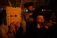 Childrend protecting himself from the heat of the bonefires during the Lag BaOmer celebrations in the orthodox distric of Mea Shearim