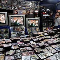 """Buhoneros - Young men sell bootleg movies and music in the Sabana Grande neighborhood of Caracas Friday, December 15, 2006.  Buhoneros, thousands of workers who sell products from clothing and accessories to household goods and bootleg DVDs make up the controversial """"informal economy.""""  While many Caracas residents complain that the buhoneros have taken over streets with their makeshift marketplace, many buhoneros give thanks to Venezuelan President Hugo Chavez for allowing them a way to survive by creating their own small businesses."""