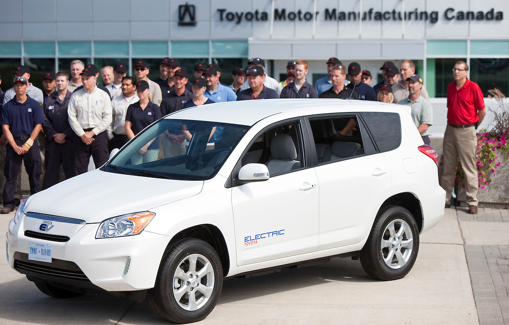 Toyota employees stand behind a RAV4 EV in front of the Toyota assembly plant in Woodstock, Ontario, Canada August 5, 2011. Toyota announced today that the electric vehicle will be assembled at the Woodstock facility starting in 2012.<br /> REUTERS/GEOFF ROBINS(CANADA)