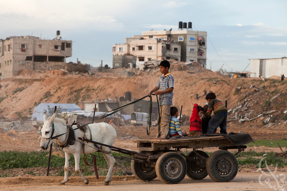 Palestinian children ride on a donkey cart past destroyed homes in the Abid Rabbo district of theJabaliya camp in Gaza December 20, 2009. A year after the Israeli military launched the controversial 22 day long Operation Cast Lead offensive against Gaza, Palestinians across the tiny strip continue to struggle daily in various ways economically, physically, and emotionally. ..