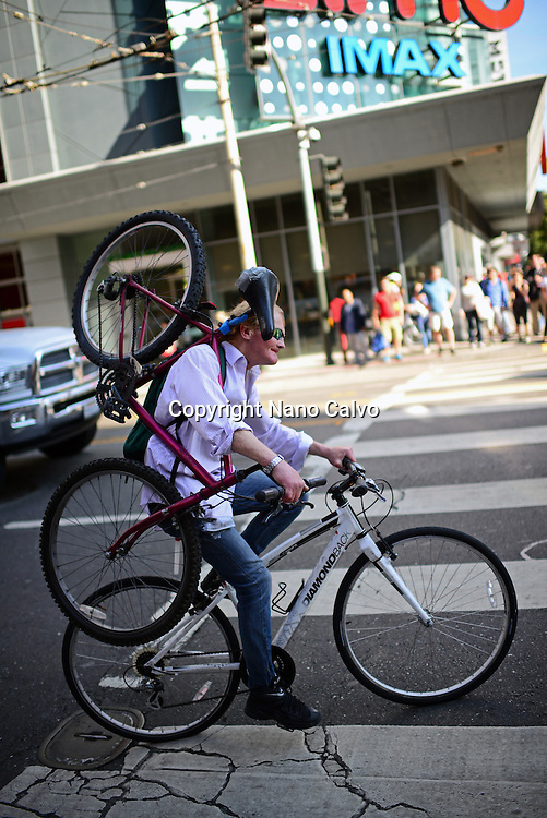 Bicycle rider carrying another bike on shoulder.