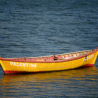 Moored open yellow with the name Valentina, on the water near Ancud, Chile.