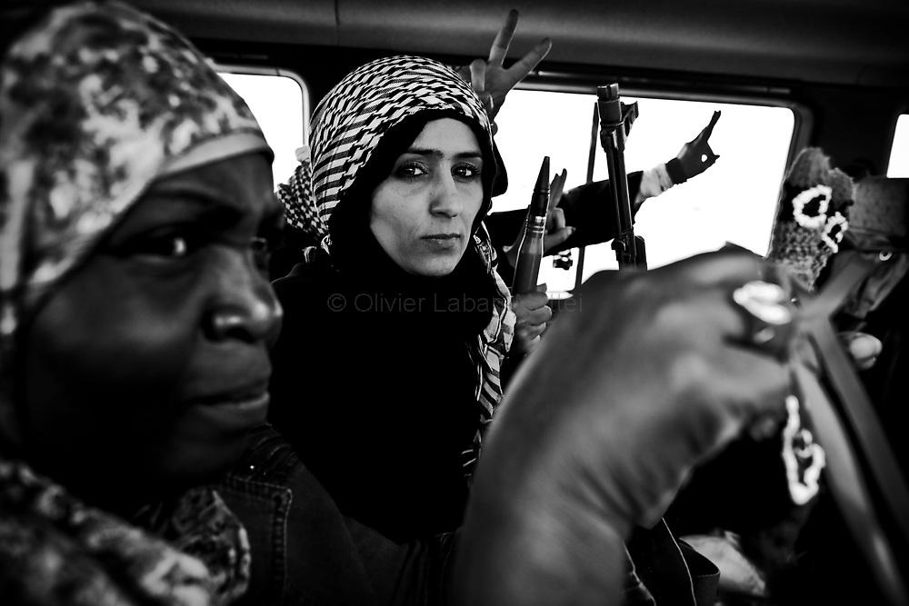 Des femmes arrivent en mini-bus sur la ligne de front près d'Aj Dabiya pour se battre aux côtés des rebelles, le 1er avril 2011.