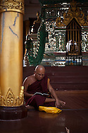 A monk reads during sunset in the Shwedagon Pagoda, the Golden Pagoda is the most sacret pagoda in Myanmar, Yangon, Burma.<br />