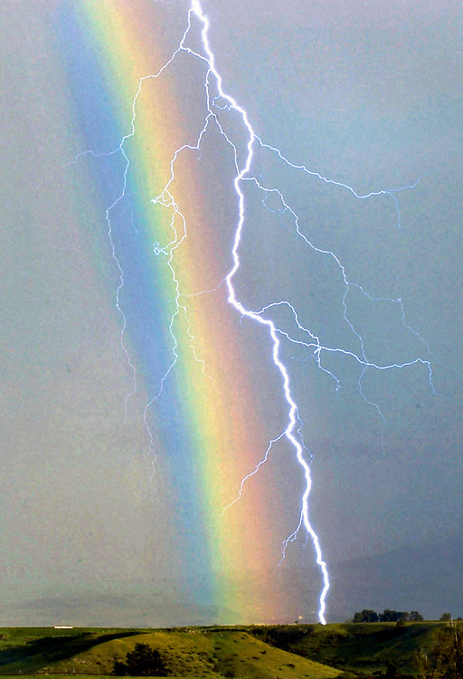 lightning bolt strikes through a rainbow during an afternoon storm ...: ryanbrennecke.photoshelter.com/image/I0000RZPvscmGzcM