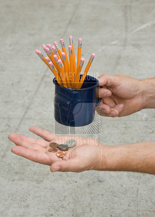 Close-up of a hand holding a cup of pencils with the other hand holding a palm of change