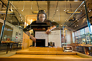 DETROIT, MI - OCTOBER, 30: Visual Merchandising employee Caitlin Barry, 30, of Royal Oak, MI, straightens this limited edition Henry Ford Pocket Watch display at the Shinola store in Detroit, Michigan, Thursday, October 30, 2014. Only 1000 were made. (Photo by Jeffrey Sauger)