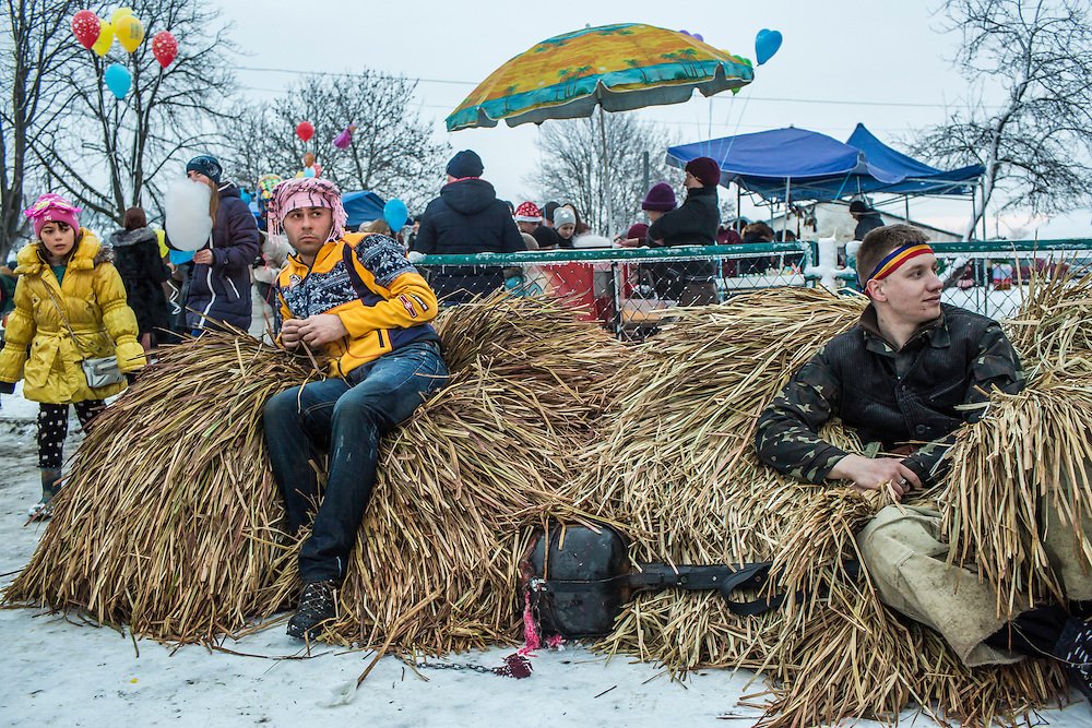 Oleksandr Perchik, 24, right, and a man who did not want to give his name rest atop elaborate bear costumes toward the end of celebrations of the Malanka Festival on Thursday, January 14, 2016 in Krasnoilsk, Ukraine. The annual festival, which consist of costumed villagers going in a group from house to house singing, playing music, and performing skits, began the previous sundown, went all night, and will last until evening.